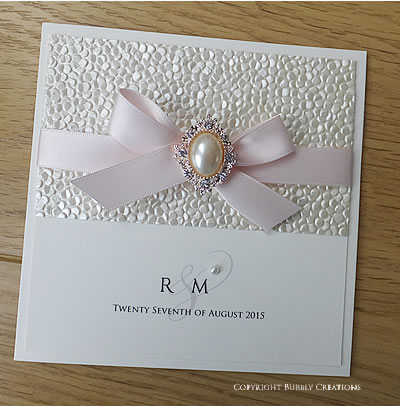 Pebble, Sequin embossed paper with satin ribbon and a gold pearl embellishment. Blush pink and ivory