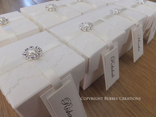 wedding favour boxes in ivory with lace, satin ribbon and a pearl and name tag
